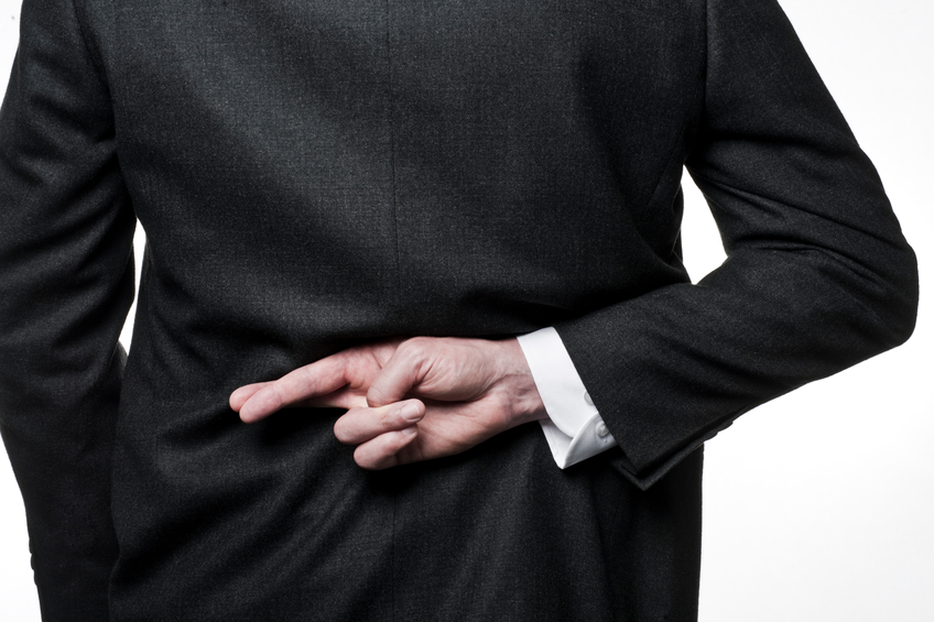 A business man with his fingers crossed behind his back, implying he is either making a wish... or telling a lie!